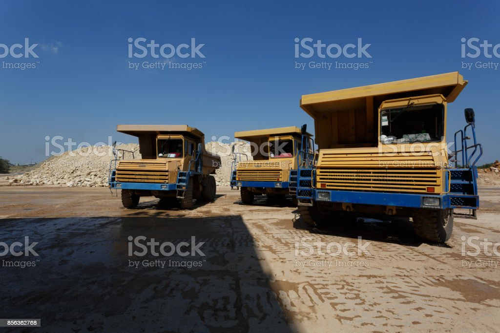 Front view of three yellow dump trucks with a shadow on a natural background. Huge transporter in a sandy quarry. stock photo