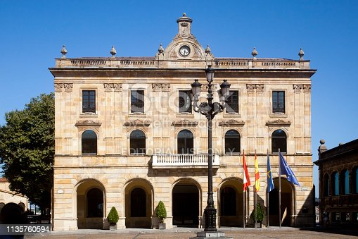 Gijon, Spain-August 31, 2018: Front view of Townhall in Gijón, Asturias, Spain. Public Government building stone facade, balcony, flags, arches, clear sky background.