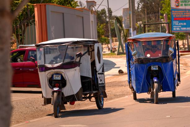 Front view of two moto-taxis New Chimbote, Peru - April 18, 2018: Front view of two moto-taxis driving down road with drivers visible three wheel motorcycle stock pictures, royalty-free photos & images