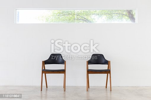 istock front view of two wooden leather chair on white concrete wall and window background. 1151016641