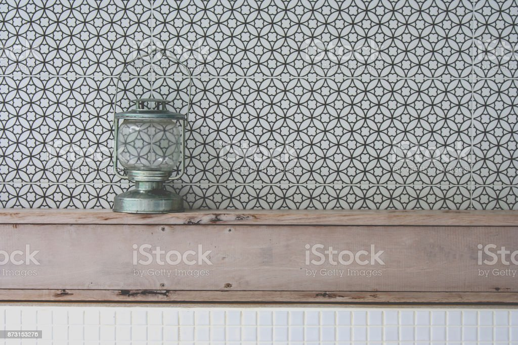 Front view of vintage kerosene oil lantern lamp setting on wooden shelf with black and grey geometric circle in the background. (Soft focus) stock photo