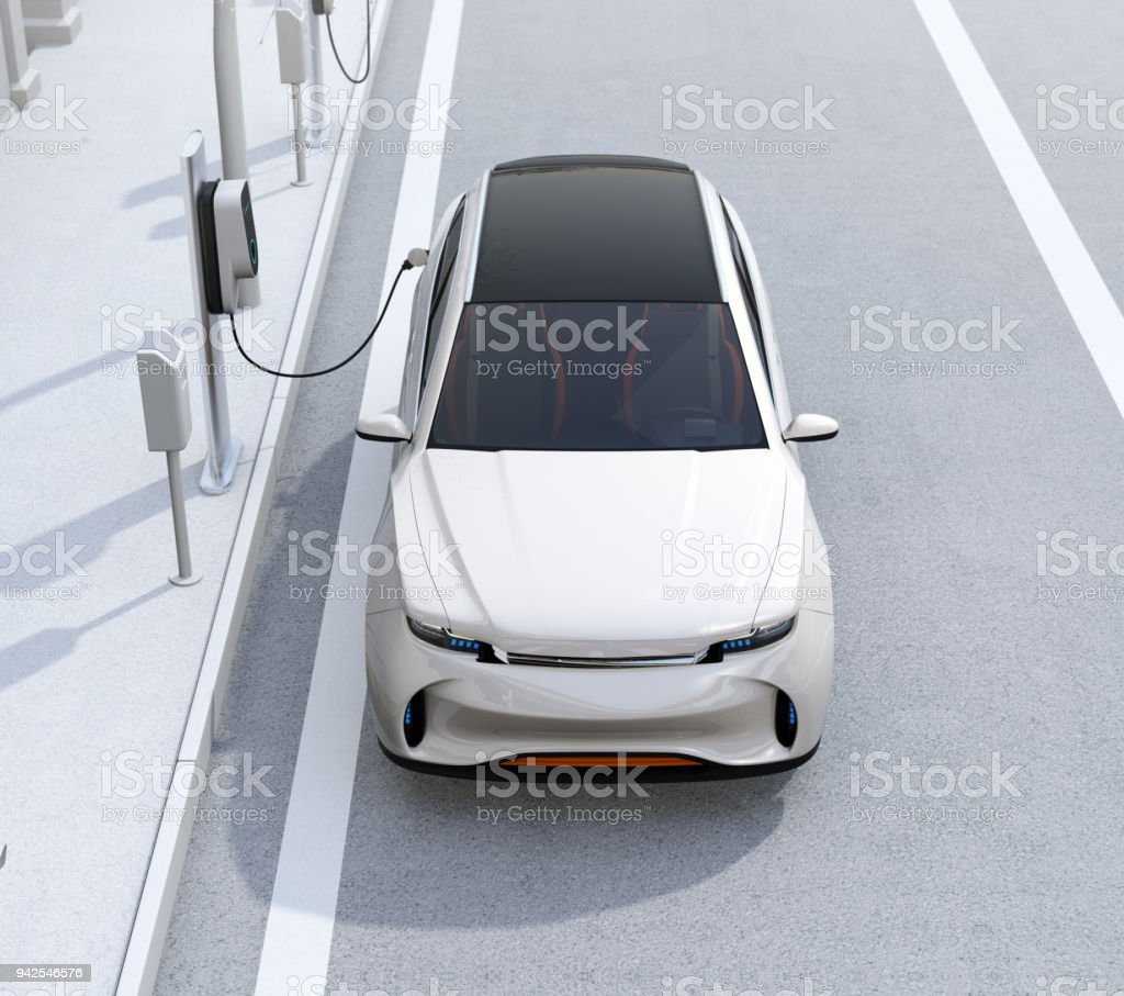 Front view of white electric SUV charging at parking lot with charging station in the street stock photo