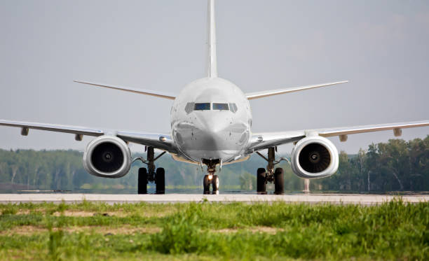 Vorderansicht des weißen Flugzeug vor dem Start auf der Piste. Passagierflugzeug hebt ab. Gewerbsmäßigen Personentransport. Mid-Range-Flugzeugen. Schmierblutungen in den Flughafen. – Foto