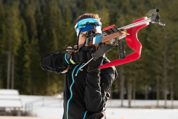 Vorderansicht des jungen weiblichen Biathlon Konkurrent üben Zielschießen, stehend – Foto