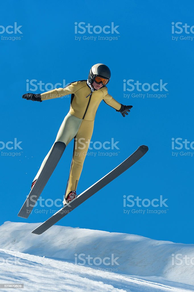 Front View of Young Male Ski Jumper Landing at 30m stock photo