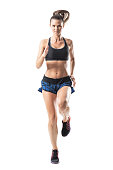 istock Front view of young pretty female athlete sprinting towards camera. 854373970