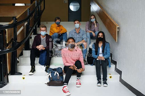 Front view of young students with face masks back at college or university looking at camera, coronavirus concept.