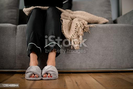front view on legs of woman which sitting on sofa with knitted blanket in black silk pajama and grey slippers