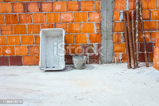 Set of different tools, equipment for brickwork with red blocks and mortar are leaning against the wall.