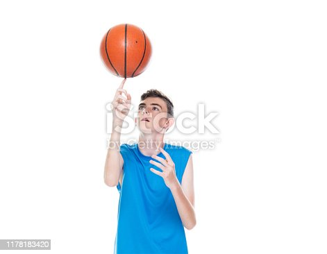 Front view / one man only / one person / full length / one teenage boy only of 12-13 years old handsome people caucasian male / young men basketball player / boys / teenage boys spinning / standing in front of white background and holding basketball - ball / using sports ball / basketball - sport / sport