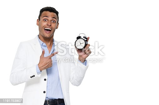 Front view / one man only / one person / waist up / portrait of 20-29 years old adult handsome people black hair african ethnicity / african-american ethnicity male / young men standing wearing pants / blazer - jacket / jacket / button down shirt / shirt who is smiling / happy / cheerful / laughing who is checking the time and holding clock with copy space
