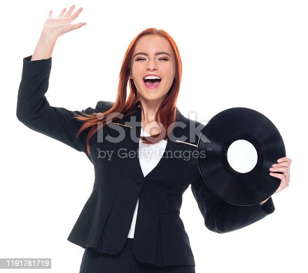 Front view / one person / waist up / portrait of 20-29 years old adult beautiful redhead / long hair caucasian female / young women businesswoman / business person dancing / exercising wearing businesswear / a suit who is smiling / happy / cheerful / laughing / joy / listening and holding record / music