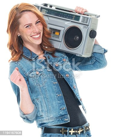 Front view / one person / waist up / portrait of 20-29 years old adult beautiful redhead / long hair caucasian female / young women dancing / exercising wearing double denim / pants / denim jacket / rolled-up sleeves / jacket / warm clothing who is smiling / happy / cheerful / laughing / joy / listening and holding boom box / personal stereo / tape recorder / music / old-fashioned / party - social event
