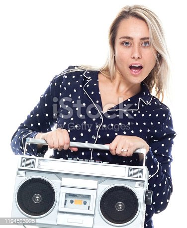 Front view / one person / waist up / portrait of 20-29 years old adult beautiful blond hair / long hair caucasian female / young women dancing / exercising wearing pajamas / nightwear who is smiling / happy / cheerful / laughing / joy / listening / cool attitude and holding boom box / personal stereo / tape recorder / music / old-fashioned / party - social event