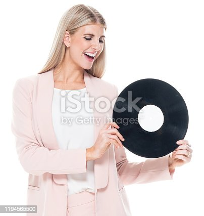 Front view / one person / waist up / portrait of 20-29 years old adult beautiful blond hair caucasian female / young women businesswoman / business person dancing / exercising wearing businesswear / business casual / smart casual / a suit who is smiling / happy / cheerful / laughing / joy / listening and holding record / music