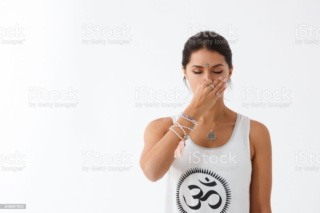 Front view portrait of beautiful young woman wearing white tank top working out against white wall, using nadi shodhana pranayama technique. Freedom, calm and yoga banner concept, copy space royalty-free stock photo