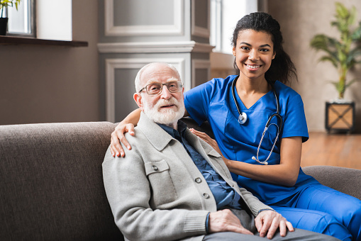 Front view portrait of caring afro nurse taking care of an elderly caucasian man grandfather grandpa indoors. Happy female doctor consulting old man in clinic.