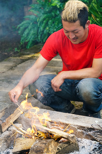 Front view Portrait of Japanese man playing with fire for barbecue