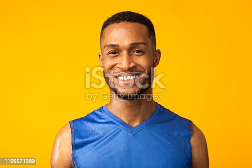 Portrait Of Happy Black Male Fitness Model Smiling At Camera Isolated Over Yellow Studio Background, Copyspace