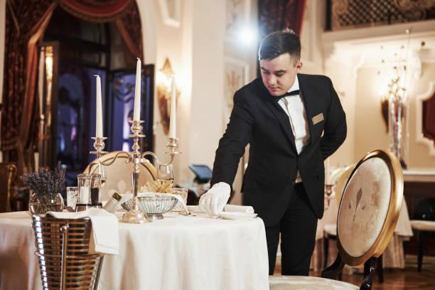 Frontansicht. Prozess der Vorbereitung von Platz für besondere Besucher. Kellner in klassischen Kleidungsarbeiten an der Serverierung – Foto