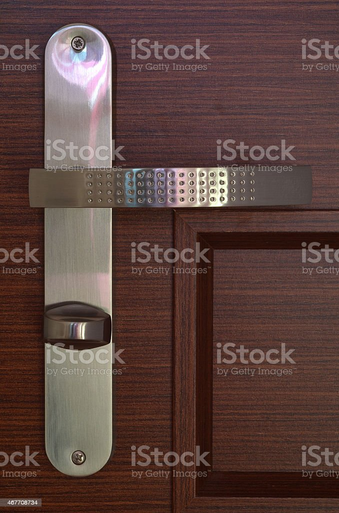 Front view to modern chrome handle on brown wooden door stock photo
