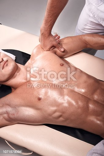 1071579572istockphoto front view, two young man, 20-29 years old, sports physiotherapy indoors in studio, photo shoot. Strong Physiotherapist hard massaging muscular patient abdomen, pushing arm with hand. 1071579394