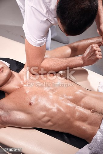 1071579572istockphoto front view, two young man, 20-29 years old, sports physiotherapy indoors in studio, photo shoot. Strong Physiotherapist hard massaging muscular patient abdomen, pushing chest and arm with elbow. 1071579442