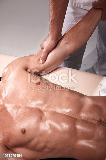 1071579572istockphoto front view, two young man, 20-29 years old, sports physiotherapy indoors in studio, photo shoot. Strong Physiotherapist massaging muscular patient arm biceps with his hands, while holding his arm. 1071579454