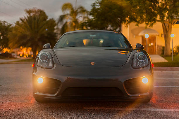 Front view with headlamps on of a Porsche Cayman Miami, USA - April 30, 2016: Full shot front view with headlamps on of a Porsche Cayman in residential area porsche stock pictures, royalty-free photos & images