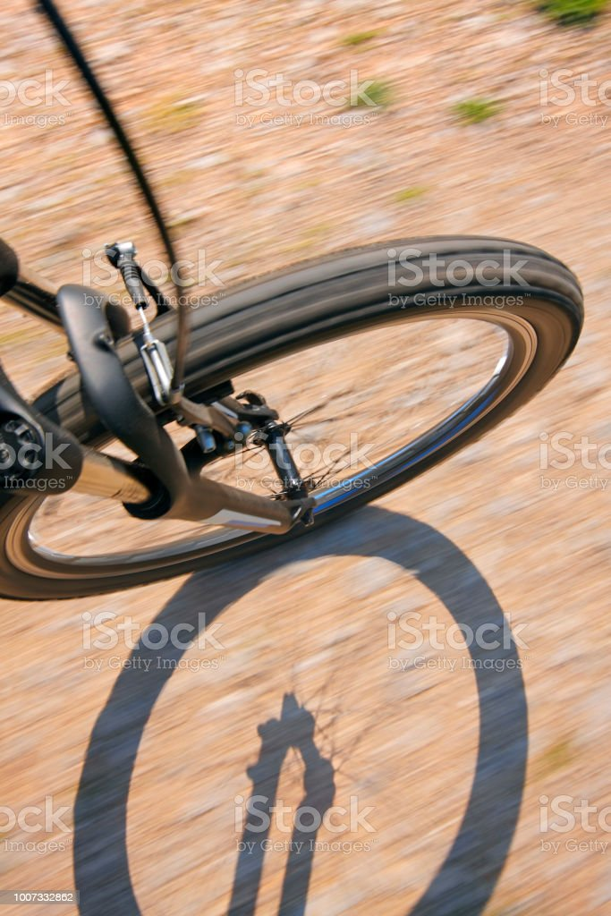 Front wheel of a bike on a dirty road stock photo