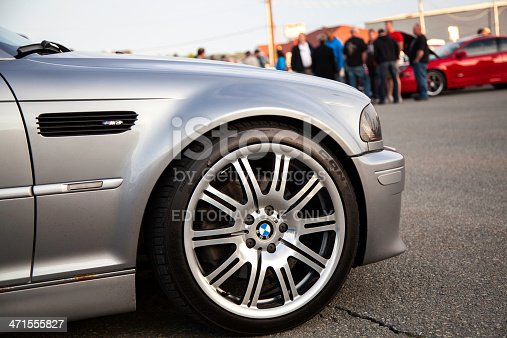 Dartmouth, Nova Scotia, Canada - June 6, 2013: The front wheel of a BMW M3 E46 while parked in a parking lot.  Wheel features the BMW logo as well as a small M logo.  People are visible in background admiring the many cars.  The E46 M3 was first introduced in 2000 and features 333 HP from a 3.2 litre engine.  The BMW M3 is considered one of the best sports cars of all time and is a benchmark in sports performance.