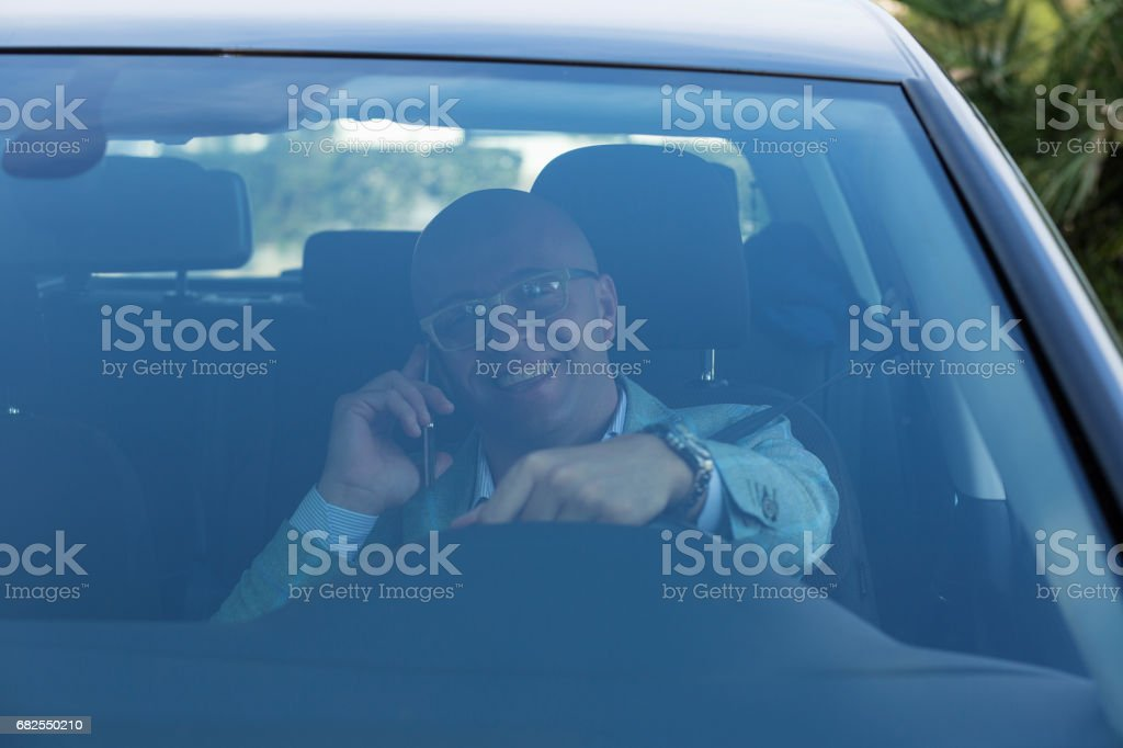 Front window view handsome young man talking on mobile phone while driving his car . Risky, reckless driver bad habits. Traffic safety rule violation lack of attention concept stock photo