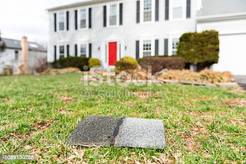 istock Front yard of house during day aftermath after storm roof tile shingle lying down on grass, damage closeup 1089130268