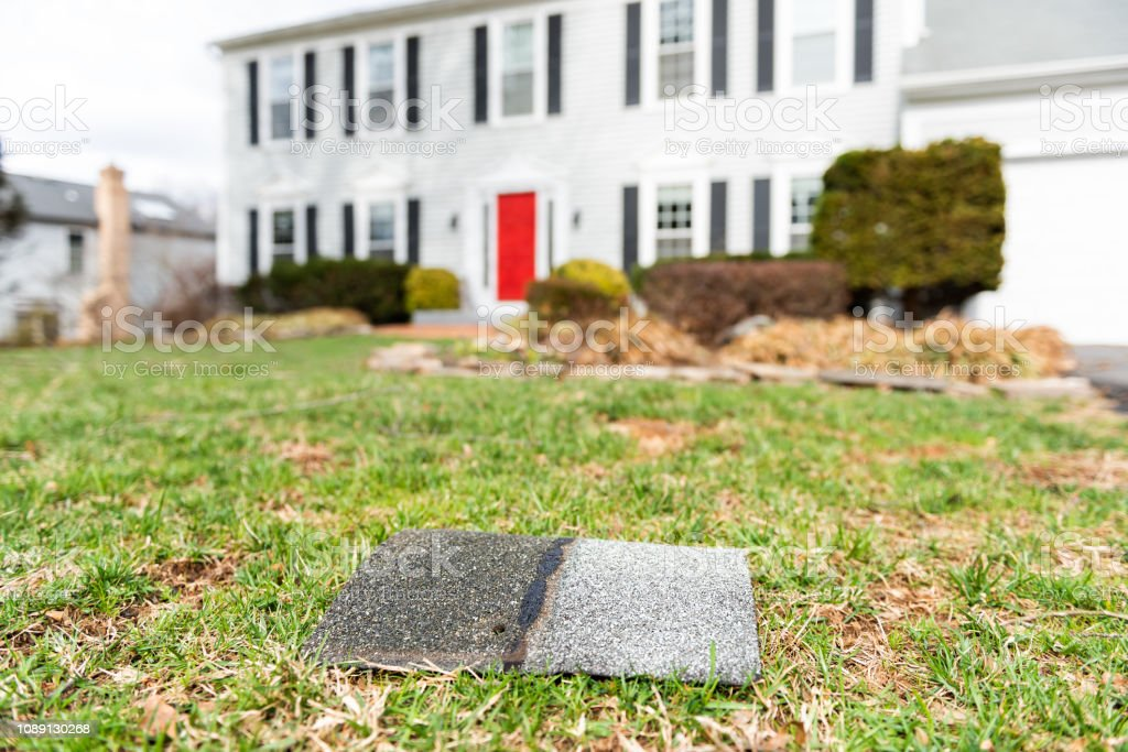 Front yard of house during day aftermath after storm roof tile shingle lying down on grass, damage closeup stock photo
