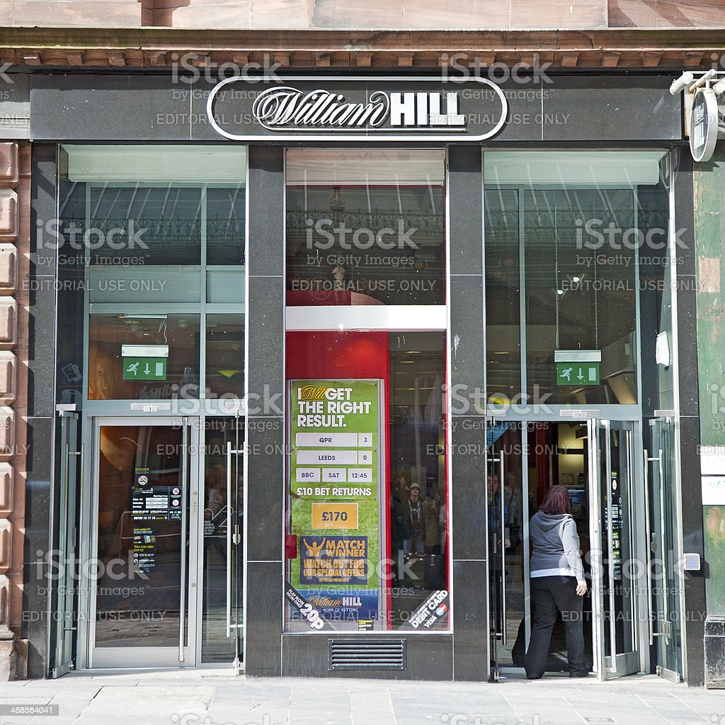 Frontage of William Hill bookmaker; woman entering stock photo