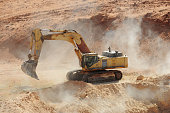 A fronthoe digger excavates sand