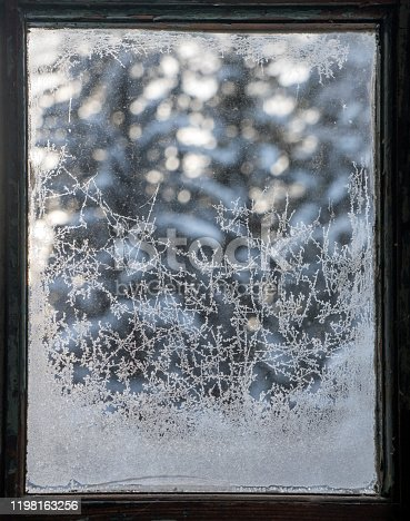Frost patterns on an old fashioned pane of window glass with trees in the background.