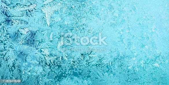 Frost on glass in window winter. pattern snow and ice