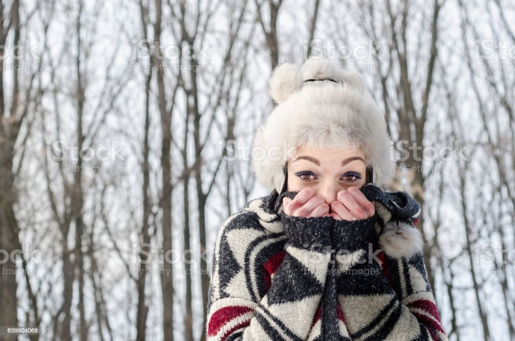 Frostbite young girl standing in the cold and warms stock photo