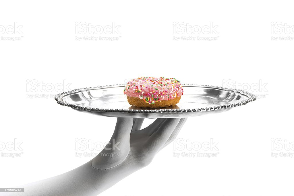 Frosted donut on silver tray held by white gloved hand-isolated on white royalty-free stock photo