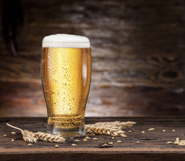 Frosted glass of beer on the wooden table. Frosted glass of beer on the wooden table. lager stock pictures, royalty-free photos & images