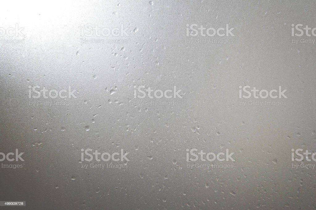 Frosted glass with water drops and bright light at corner stock photo