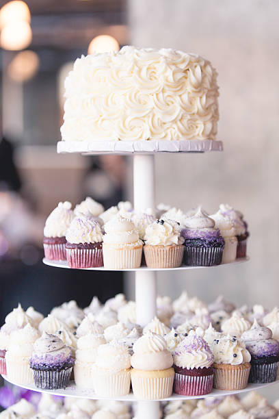 Frosted Mini Cupcakes Displayed with Small Cake on Cake Stand stock photo
