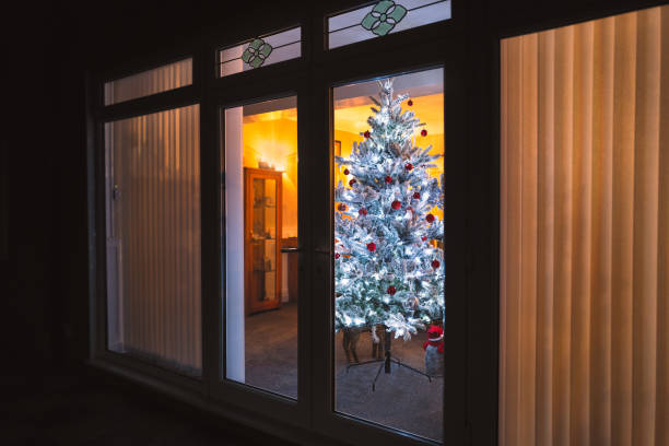 A frosted white artificial christmas tree with red and silver decorations seen through large patio doors with vertical slat blinds and bevel window designs. stock photo