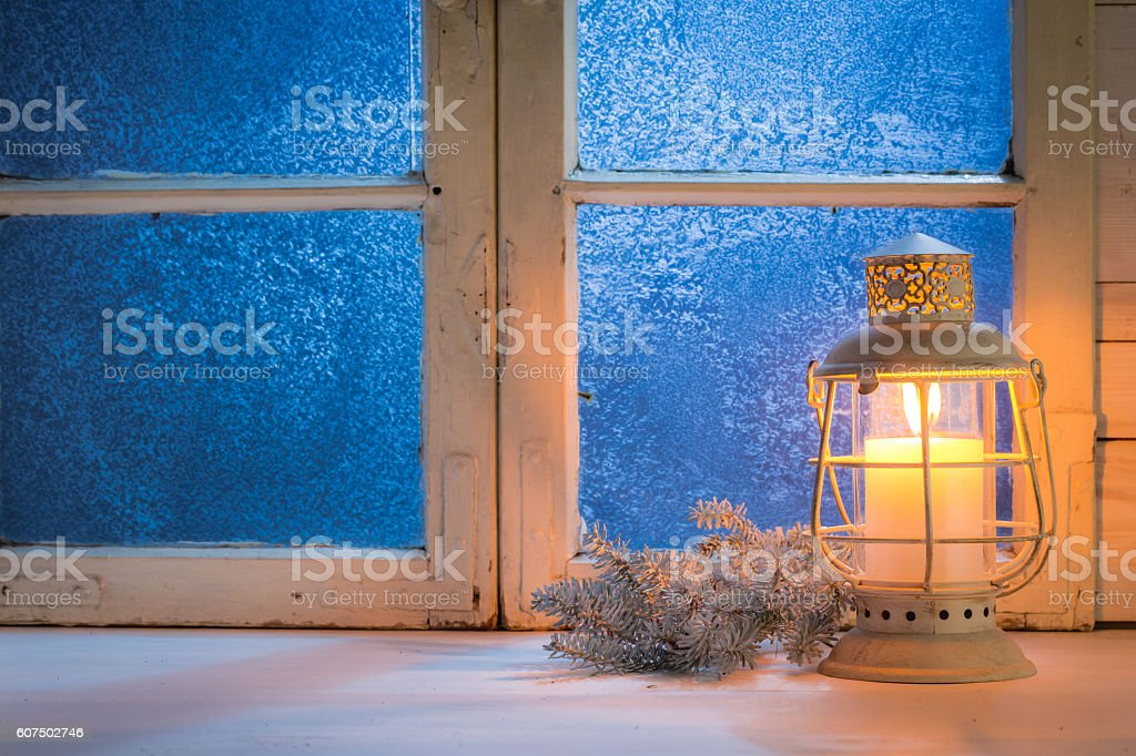 Frosted window with candle for Christmas stock photo