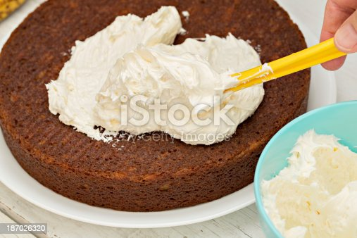 A high angle close up shot of a hand applying cream cheese  frosting on a freshly baked banana cake