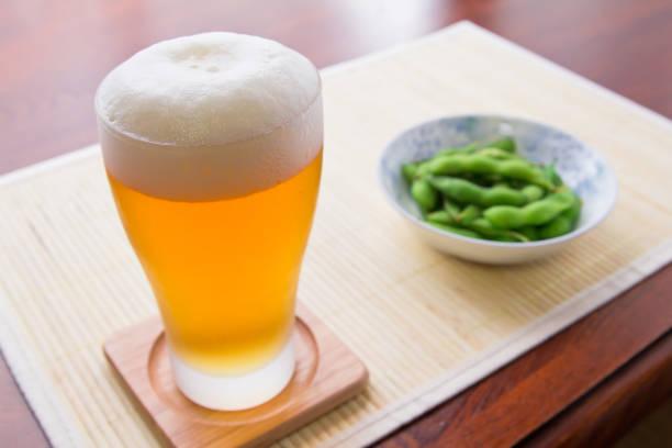 ビールとゆでた枝豆の冷ややかなガラス - ビール ストックフォトと画像