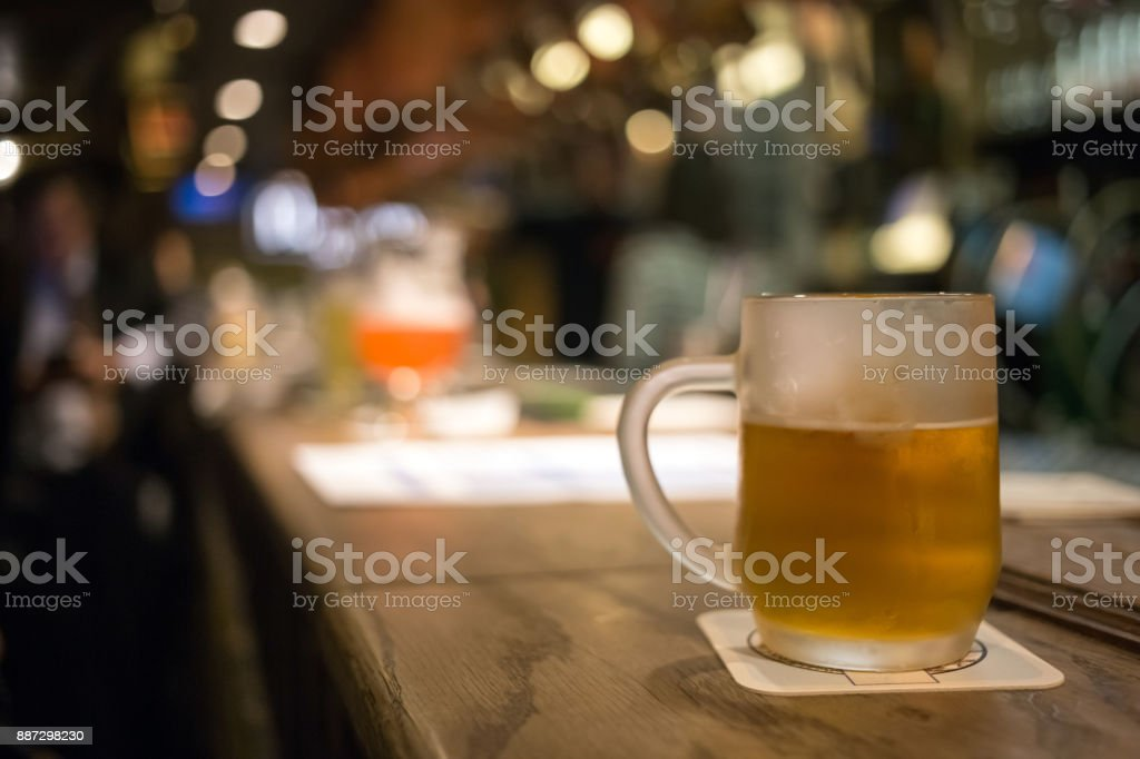 Frosty glass of light beer on the bar counter. Beer tap in Brussel Belgium stock photo