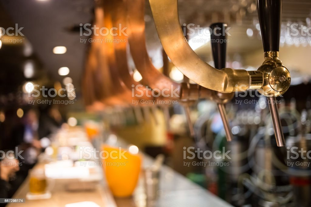 Frosty glass of light beer on the bar counter. Beer tap stock photo