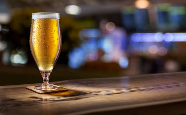 Frosty glass of light beer on the bar counter. Behind blurred background. stock photo